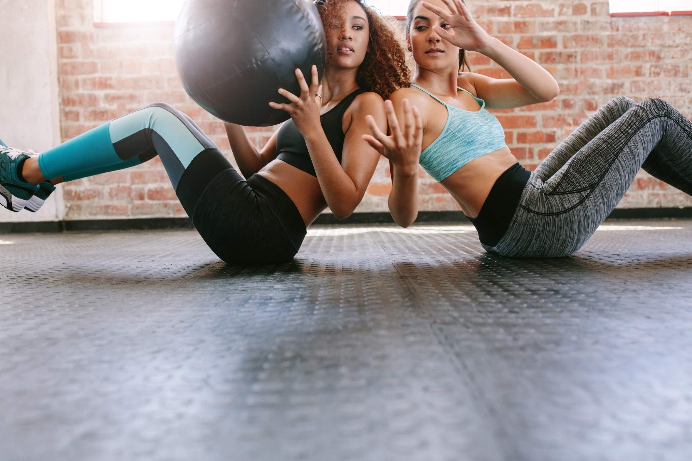 Kobiety ćwiczące w piłką lekarską w studiu treningu personalnego.