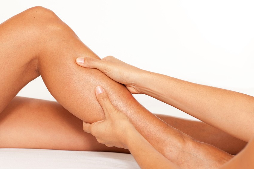 Masażysta wykonuje drenaż limfatyczny najskuteczniejszą metoda walki z obrzękami nóg, w szczególności łydek.
