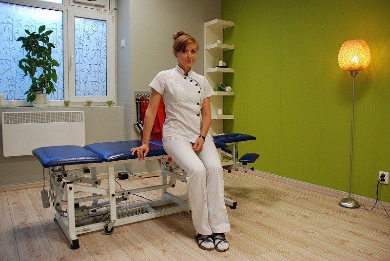 Fizjoterapeutka oczekująca na pacjenta w gabinecie rehabilitacyjnym.