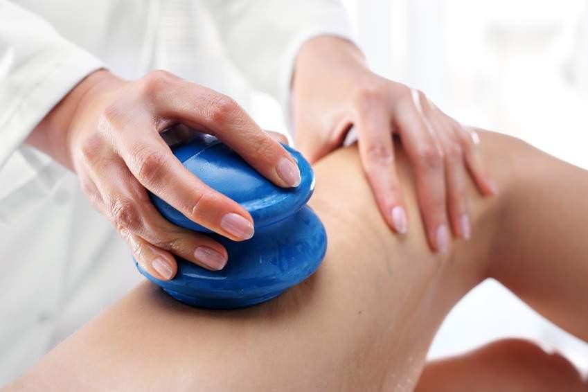 Masażystka wykonująca masaż bańką chińską uda, masaż ogumowanymi bańkami do masażu, RehaFit