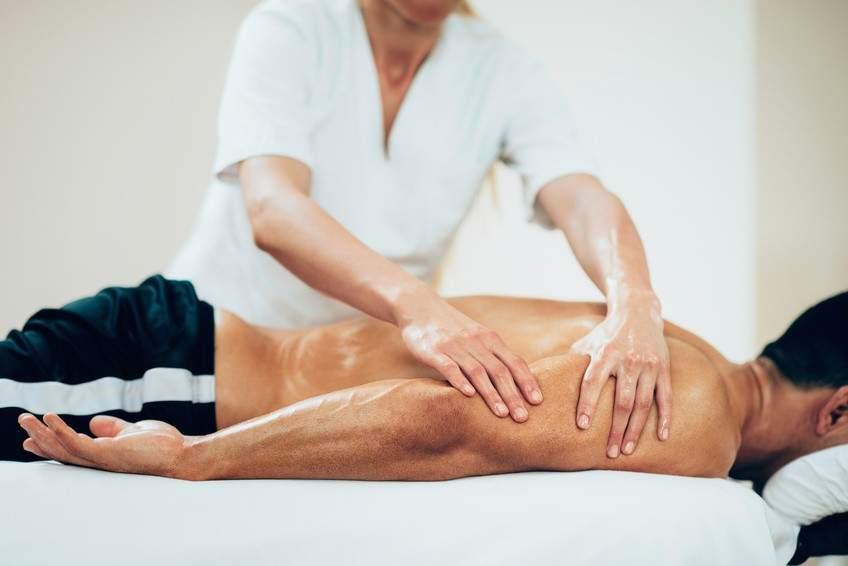Wysportowany mężczyzna podczas masażu sportowego po ćwiczeniach na siłowni w RehaFit we Wrocławiu. Kompleksowa rehabilitacja sportowa.