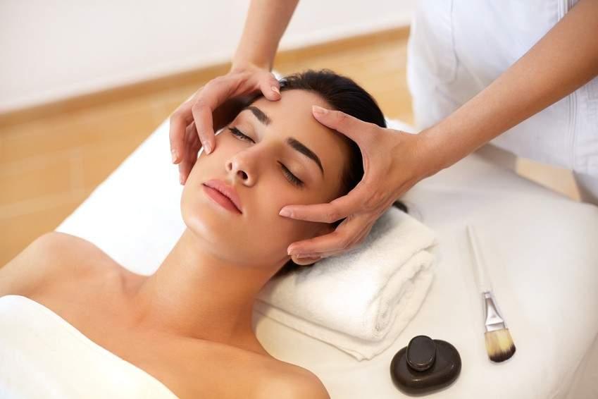 Masażystka wykonuje odprężający masaż twarzy, szyi i dekoltu w centrum masażu RehaFit we Wrocławiu.