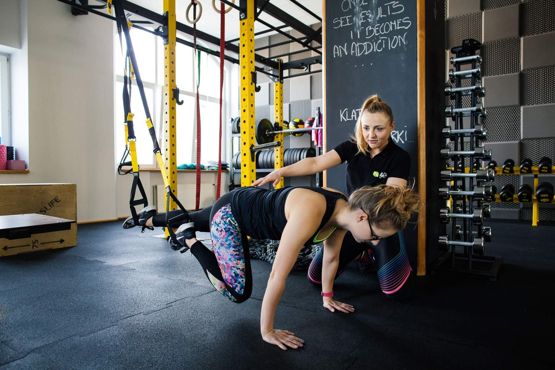 Trenerka personalna podczas instruktażu klientki w ćwiczeniach mięśni brzucha na TRX.