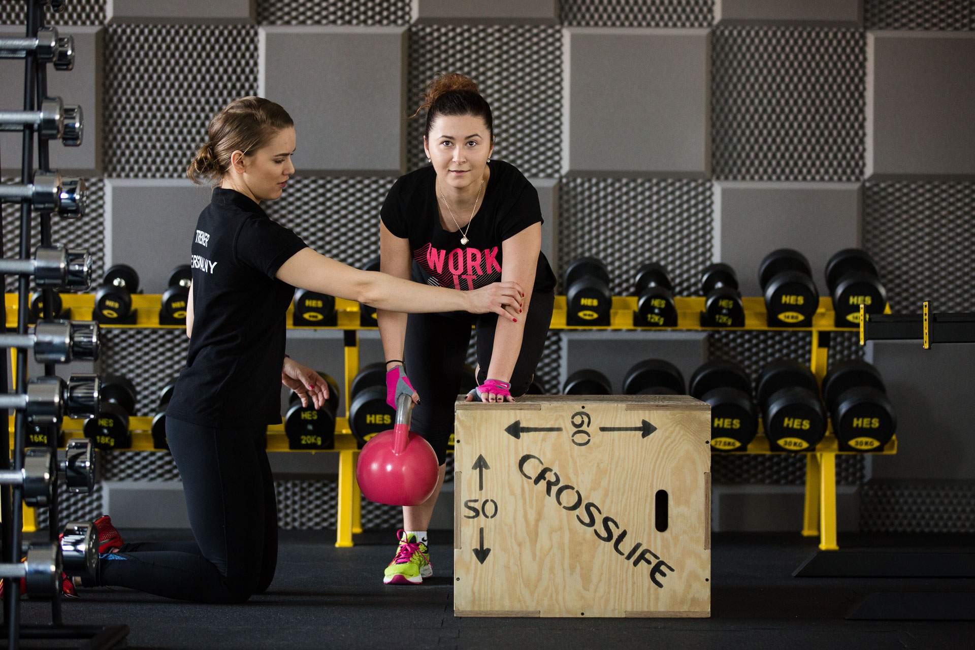 Kobieta wraz z trenerką osobistą ćwiczy z użyciem kettleball mięśnie pleców.