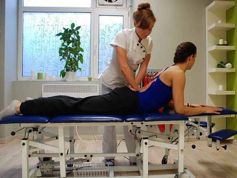 Rehabilitantka podczas rehabilitacji kręgosłupa u pacjentki z dyskopatią kręgosłupa.