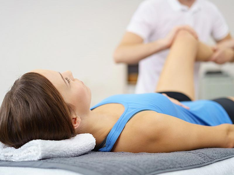 Pacjentka ćwicząca staw kolanowy wraz z fizjoterapeutą.