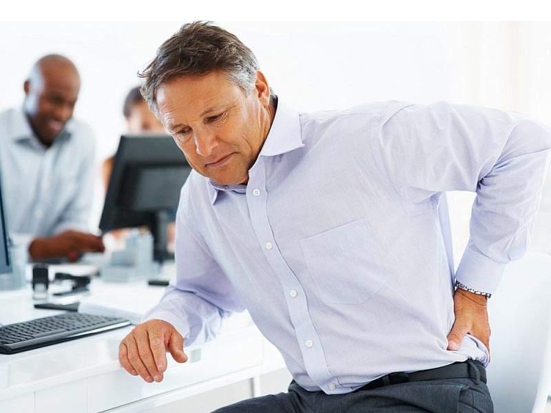 Mężczyzna w biurze z bólem kręgosłupa lędźwiowego.