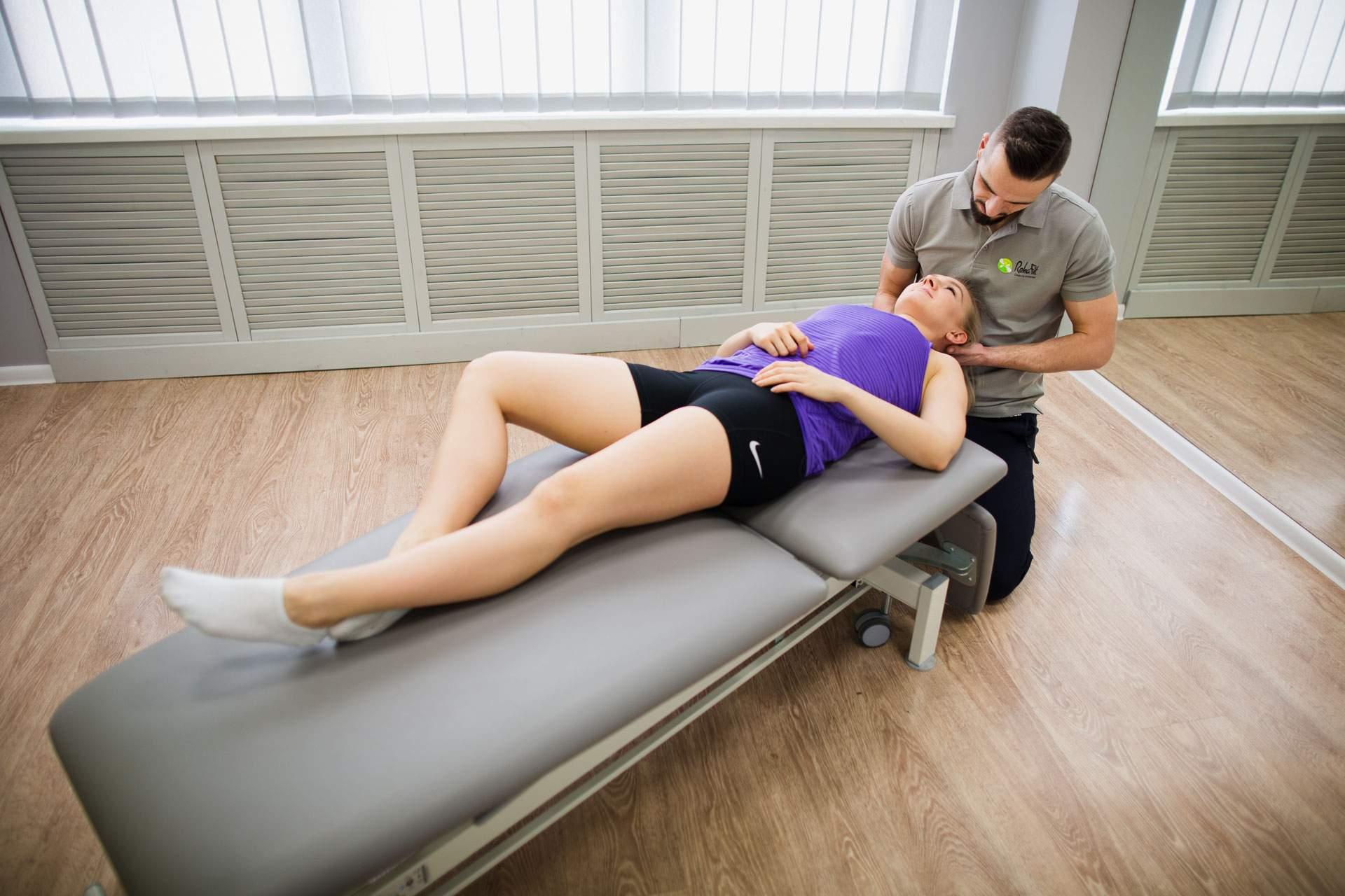 Fizjoterapeuta z RehaFit wykonujący terapię manualną u pacjentki z bólami kręgosłupa szyjnego.