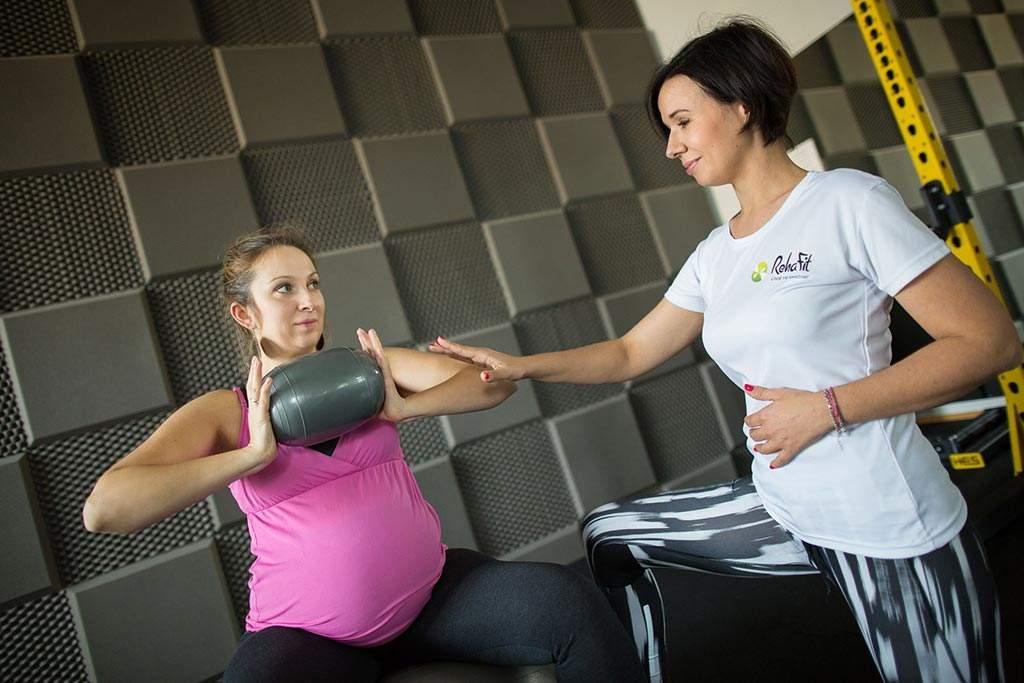 Kobieta w ciąży podczas treningu pod okiem trenera personalnego z centrum RehaFit we Wrocławiu. Pomożemy Ci zdrowo przygotować się do porodu.