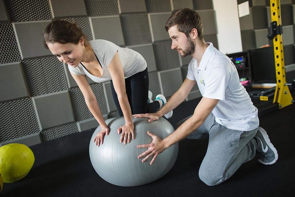 Fizjoterapeuta podczas terapii leczniczej pacjentki ukierunkowanej na ćwiczenia stabilizacyjne tułowia.