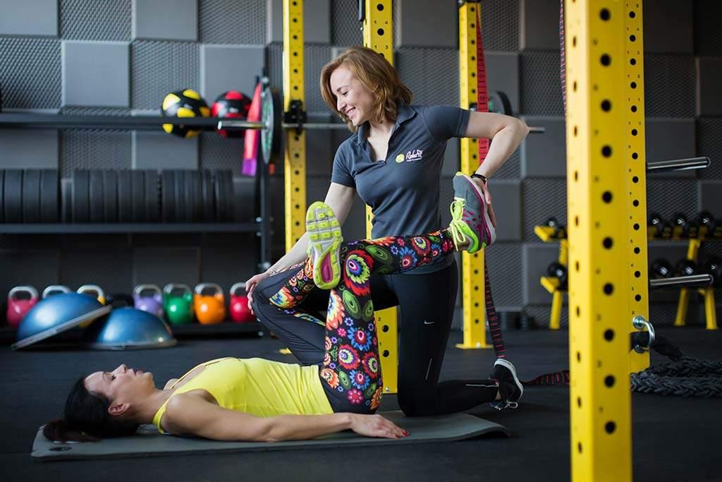 Fizjoterapeutka podczas medycznego treningu rehabilitacyjnego w nowocześnie wyposażonym studiu treningu RehaFit we Wrocławiu.