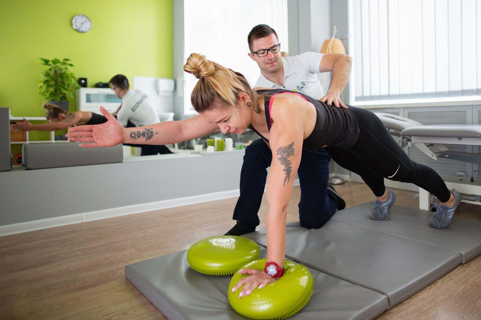 Fizjoterapeuta podczas indywidualne pracy z pacjentem mającej na celu poprawę stabilizacji oraz wzmocnienie mięśni tułowia.