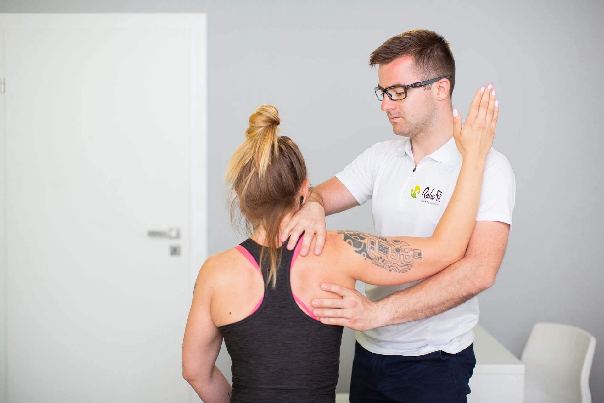 Fizjoterapeuta podczas badania stawy ramiennego u pacjetnki aktywnej fizycznie.