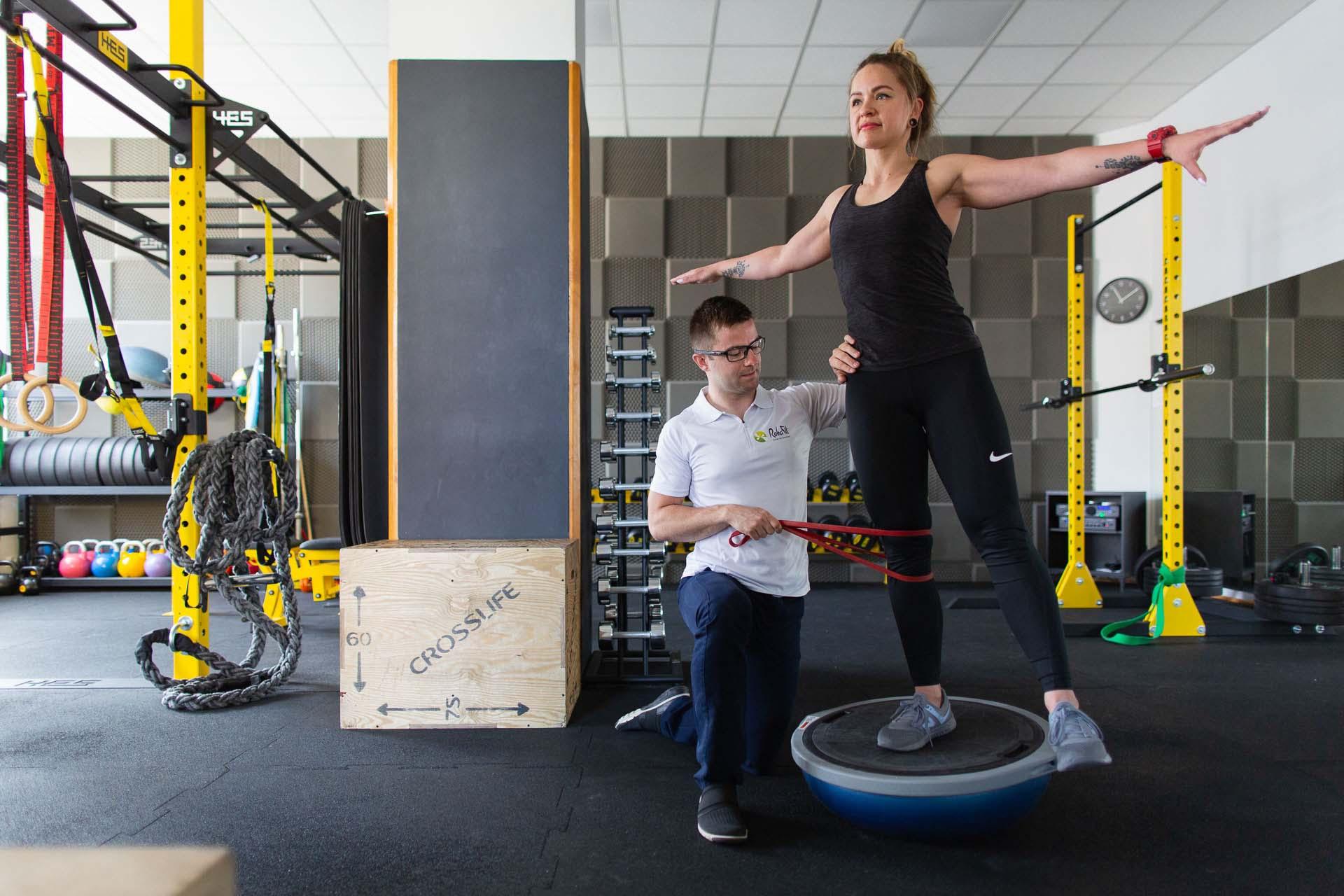 Fizjoterapeuta w trakcie medycznego treningu rehabilitacyjnego mającego na celu poprawę stabilności kończyny dolnej u pacjentki aktywnej fizycznie.